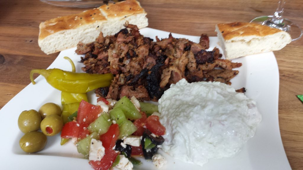 Gyros mit Beilagen (griech. Salat, Zaziki, Oliven, Peperoni und Fladenbrot)