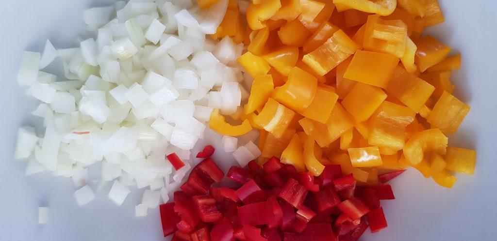 Paprika, Zwiebel und Chili kleinschneiden